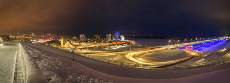 Picturesque winter panorama of the night city with houses, snow, street lights, a church and a bridge with blue illumination against a dark sky with clouds