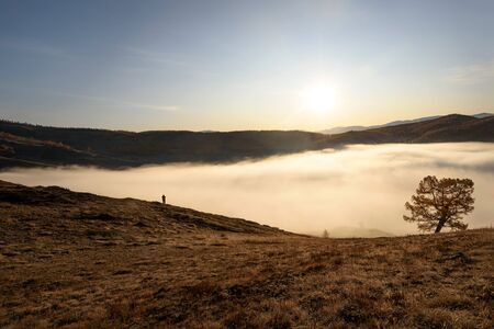 Amazing autumn top view o the mountains covered with snow and forest, dense fluffy fog over the lake and a small silhouette of a tourist at sunrise. Altai, Russia Standard-Bild - 140373468
