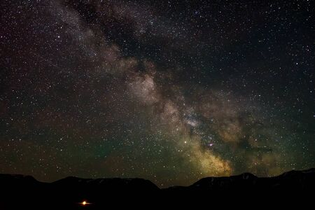 Night panorama of the starry sky with the Milky Way galaxy, stars, nebulae and meteors in the mountains