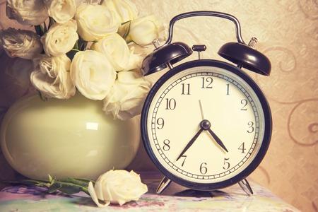ikebana: vintage retro clock  and ikebana on table Stock Photo