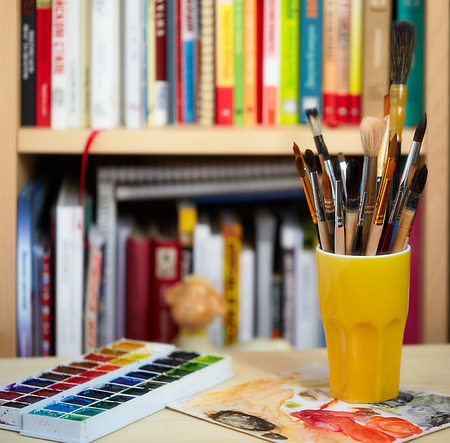 Photo of brushes in the glass and watercolors on blurred bookshelves background. Фото со стока