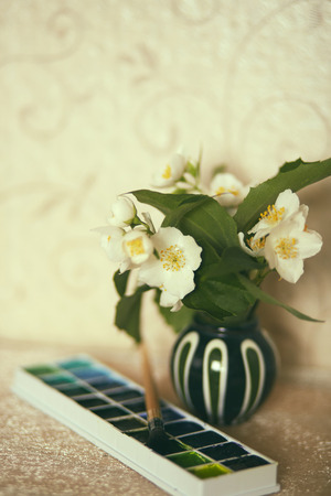 Vintage retro photo of jasmine flowers in little vase with a watercolor box and a brush Фото со стока
