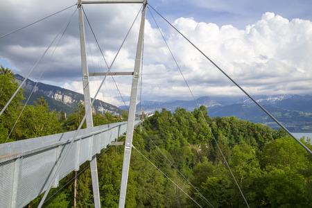 modern suspension bridge stretched between the mountains in Thun, Switzerland Фото со стока