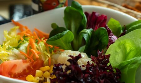 Fresh salad with cauliflower, carrots, corn, tomatoes. Homemade food. The concept of delicious and healthy food. Close-up. In a white dish.