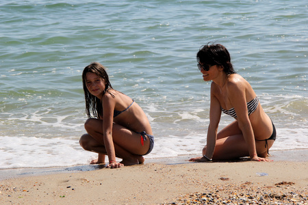 mother and daughter on the beach near the sea. photo