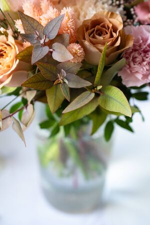 Bouquet of different flowers in a glass vase on the table