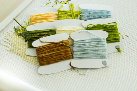 punto de cruz: A set of embroidery threads in natural colors on paper reels. Selective focus. Close-up. Foto de archivo