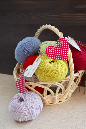 Colored balls of acrylic yarn in a basket decorated with hearts. Gift for Valentines Day needlewomen. Selective focus. Vertical.