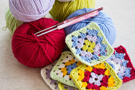Colored balls of wool, crochet hook and knitted fragments on a light background. Selective focus. Stock Photo