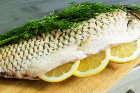 Fresh raw fish with lemon and dill, prepared for baking. Selective focus.