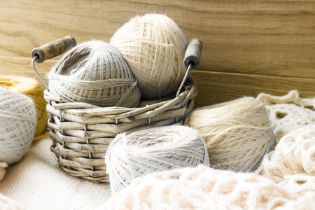 Balls of wool yarn in a wicker basket. Threads for needlework. Image in sepia tones.