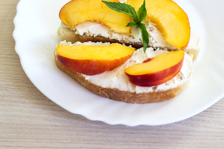 Sandwich with cream cheese and nectarines. Fruit sandwich on a white plate. Banco de Imagens