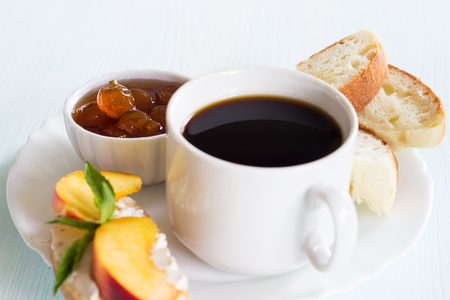 Coffee, jam wheat bread and a sandwich with cream cheese. Traditional breakfast on a light background. Copy space.