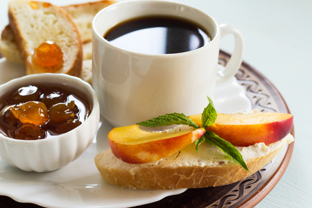 Coffee, jam wheat bread and a sandwich with cream cheese. Traditional breakfast on a light background. Copy space. 版權商用圖片 - 107415716
