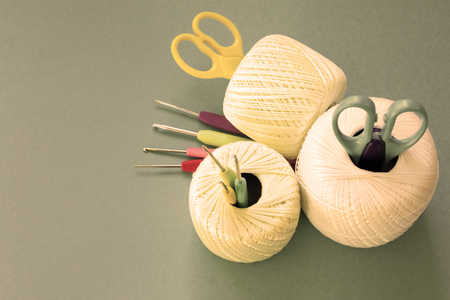 Balls of yarn, knitting needles, scissors, crochet hooks. Materials and tools for needlework. The concept of earning needlework. Image in sepia tones. Foto de archivo