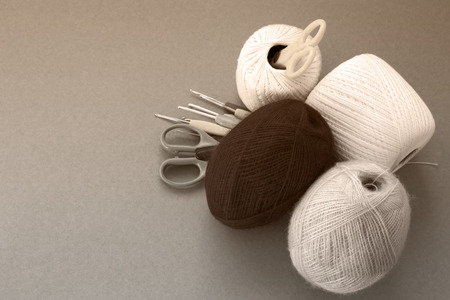 Balls of yarn, knitting needles, scissors, crochet hooks. Materials and tools for needlework. The concept of earning needlework.  Image in sepia tones.