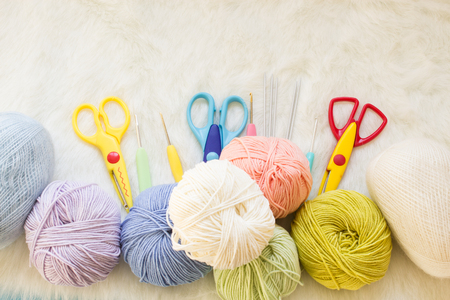 Multicolored balls of yarn, scissors, knitting needles, hooks. Materials for creativity and crafts. Concept of a woman's hobby. Knitting and work at home. Zdjęcie Seryjne
