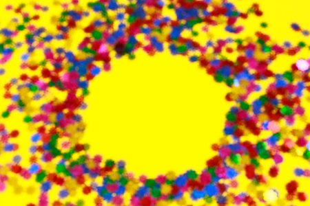 Blurred focus. Colorful confetti scattered on a yellow background. Place for text. Copy space.
