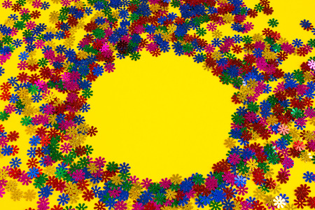 Colorful confetti scattered on a yellow background. Place for text. Copy space.
