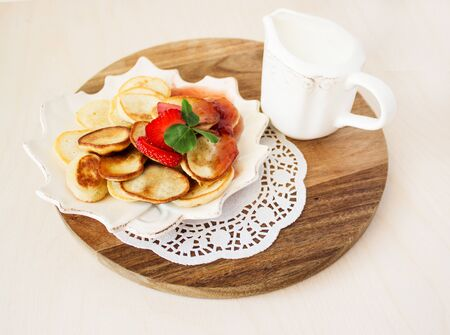 Homemade pancakes for breakfast. Traditional breakfast with pancakes, cream and strawberry jam and strawberries. Close-up. View from above. 写真素材