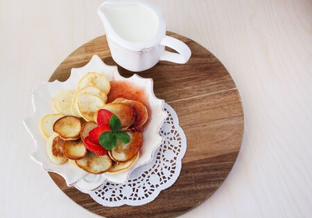 Homemade pancakes for breakfast. Traditional breakfast with pancakes, cream, strawberry jam and strawberries. Place for text.