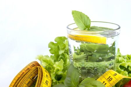 Clean water, salad, tape measure and cutlery on a white background. The concept of healthy eating and losing weight. Sports nutrition.