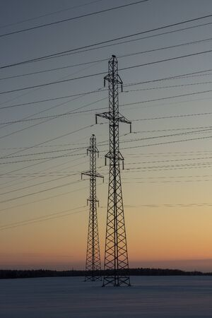 Power lines on a background of a winter sunset. Winter landscape.