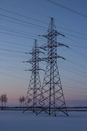 Power lines against the backdrop of winter dawn. Winter landscape. Dawn. Copy space.
