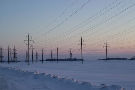 Power lines on a background of a winter sunset. Winter landscape. Copy space.