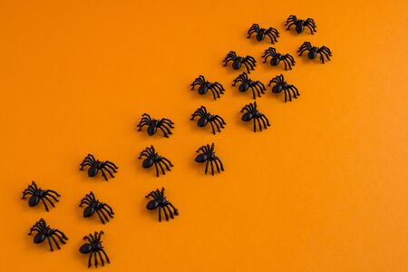 Halloween background. Traditional halloween decor. Spiders on an orange background. Place for text.