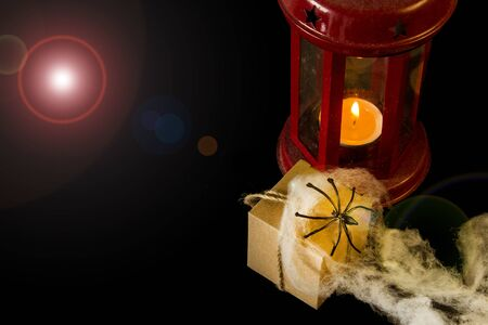 Halloween background. Red lantern, gift, spider and cobweb on a black background. Halloween party concept. Place for an inscription.