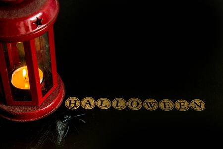 Halloween background. Red lantern, the inscription halloween, spider and cobweb on a black background. Halloween party concept.