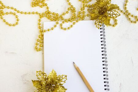 Flat lay of christmas wish book, pencil and gold jewelry. The concept of planning wishes for the winter holidays. Cozy decorations for the winter holidays. Copy space.
