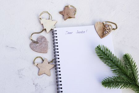 Blank sheet for writing christmas wishes. Concept for planning Christmas and New Year wishes and setting goals for next year. Flat layout of luxurious Christmas decorations and notebook.