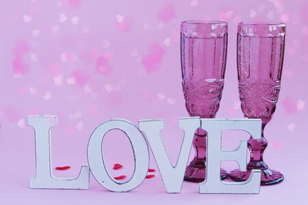 Valentines day concept. Glasses with champagne and a love inscription on a pink background. Beautiful festive background with place for text. Stok Fotoğraf
