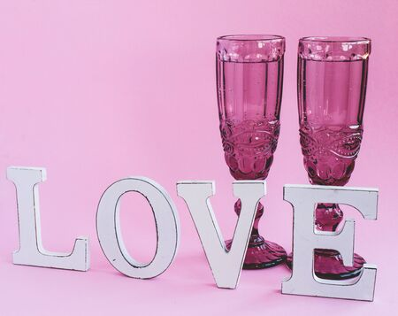 Glasses with champagne and a love inscription. Valentines day concept.