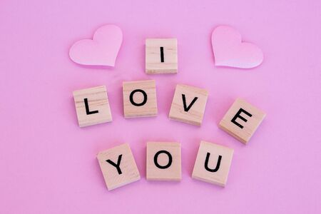 Lettering I love you in wooden letters on a pink background. Фото со стока