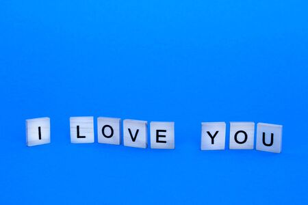 The inscription I love you in wooden letters on a blue background. Фото со стока
