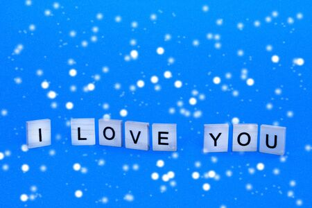 Text i love you on blue background. Background for Valentines Day. The concept of romance in love. Фото со стока