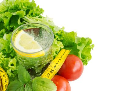 Pure drinking water with lemon, lettuce and tape measure. The concept of a healthy diet and drinking regime. Body cleansing and weight loss program. Copy space.