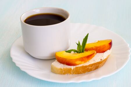 Black coffee, sandwiches with cream cheese, peach and fresh mint. The concept of proper nutrition. Traditional breakfast. Close-up.