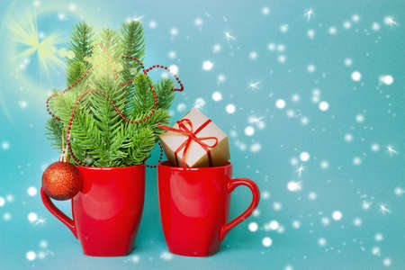 Christmas and New Year. Christmas composition with a red mug, branches of a Christmas tree and a gift box. Blank for a Christmas card. Copy space.