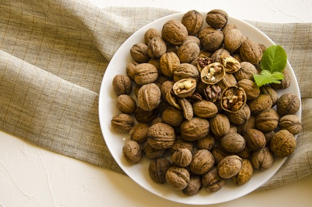 Plate with tasty walnuts on white background