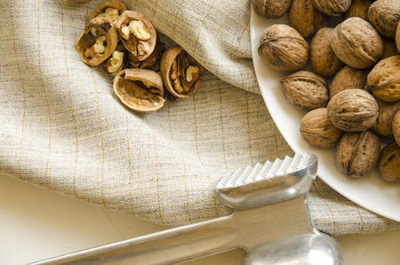 Plate with tasty walnuts and hammer on white background