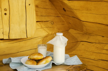 Fresh milk in a glass bottle and a glass, next to the pies on a wooden table. The concept of healthy organic products. Rusty style. Plaic Still Life for text. Close-up.