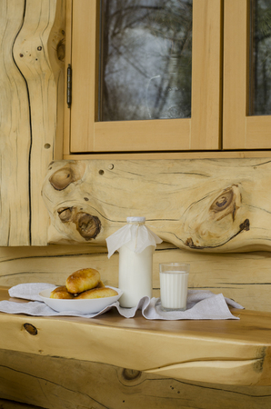 Fresh milk in a glass bottle and a glass, next to the pies on a wooden table. The concept of healthy organic products. Rusty style. Plaic Still Life for text.