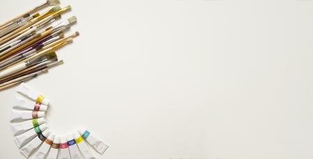 Auf einem weißen Hintergrund in der oberen linken Ecke befinden sich Pinsel verschiedener Größe, darunter sind Aquarellfarben von zwölf Farben im Halbkreis in der unteren linken Ecke. Vorbereitung auf die Kunstschule. Liebe zur Kunst.