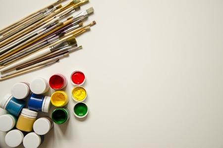 Auf einem weißen Hintergrund in der oberen linken Ecke befinden sich Pinsel verschiedener Größe, darunter in der unteren linken Ecke Farben (Gouache) von zwölf Farben. Geöffnet drei Farben rot, gelb und grün. Vorbereitung auf die Kunstschule. Kinder und Kreativität.