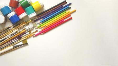 Auf weißem Hintergrund in der oberen linken Ecke Farben (Gouache), darunter Pinsel in verschiedenen Größen und Buntstifte in zwölf Farben. Vorbereitung auf die Kunstschule. Kinder und Kreativität. Freier Speicherplatz für Aufzeichnungen.