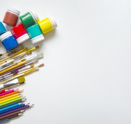 Auf einem weißen Hintergrund von links von oben sind Farben (Gouache) drin, darunter Pinsel in verschiedenen Größen und Buntstifte in zwölf Farben. Vorbereitung auf die Kunstschule. Kinder und Kreativität. Freier Speicherplatz für Aufzeichnungen.